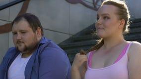 Mollig meisjes tollend haar die, actief met vet onzeker mannetje, gevoel flirten stock footage