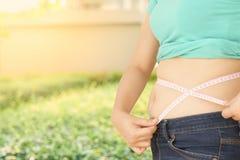 Mollige Frau, die versucht, ihren eigenen fetten Bauch zu messen stockbilder