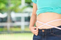 Mollige Frau, die versucht, ihren eigenen fetten Bauch zu messen stockfoto