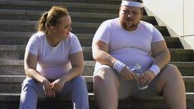 Mollige man en vrouw die na harde training op treden rusten, die zwaar ademen stock video