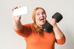 Mollige vrouwensport thuis status geïsoleerd op wit die selfie foto's met opgewekte domoor nemen stock foto's