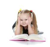 Molliges kleines blondes Mädchen, das ein Buch an liegt liest Lizenzfreie Stockfotografie