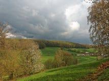 Moln över en dal och en lantgård Royaltyfri Bild