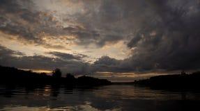 Moln över floden och solnedgången i aftonen Arkivbild