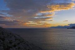 Moln över havet exponerat av inställningssolen fotografering för bildbyråer