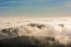 Moln över maxima av ett berg arkivfoto