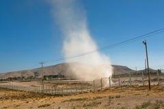 Moln av damm och sand som någonstans lyfts av tromben av vägen i bergen av Mellanösten Arkivfoto