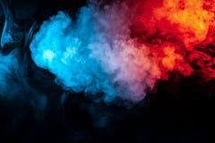Moln av isolerad kulör rök: blått rött, apelsin som är rosa; bläddra på en svart bakgrund i mörkret royaltyfria bilder