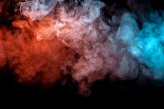 Moln av isolerad kulör rök: blått rött, apelsin som är rosa; bläddra på en svart bakgrund i mörkret arkivfoto