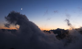 Moln dimma måne- och bergmaxima på solnedgången, Monte Rosa, fjällängar Royaltyfria Bilder