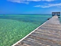 Moln för blå himmel och vitöver en tropisk pir, att sträckt ut in till kristallblåtthavet Cayo Guilermo, kuban gömma i handflatan arkivbild