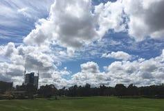 Moln, himmel, fält och byggnad Arkivbild