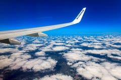 Moln, himmel och jord som sett igenom fönster av ett flygplan Royaltyfria Foton