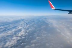 Moln, himmel och vinge som sett igenom fönster av ett flygplan Arkivfoton