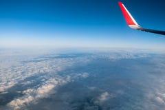 Moln, himmel och vinge som sett igenom fönster av ett flygplan Royaltyfria Foton