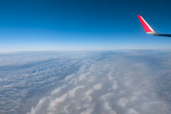 Moln, himmel och vinge som sett igenom fönster av ett flygplan Royaltyfri Fotografi