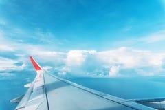 Moln-, himmel- och vingflygplan som sett igenom fönster av ett flygplan Arkivbild