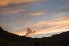 Moln i bakgrundskonturn av bergen på solnedgången Royaltyfri Bild