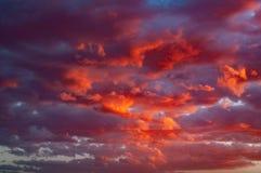 Moln i en röd kulör solnedgång i den Colorado ökenplatån på Tuba City, Förenta staterna arkivfoto