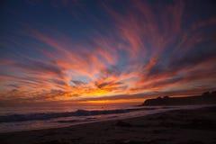 Moln i flammasolnedgång i San Simon sätter på land, CA royaltyfria foton
