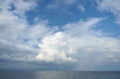 Moln i himlen ovanför havet arkivfoton