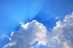 Moln med mörka solstrålar arkivbild