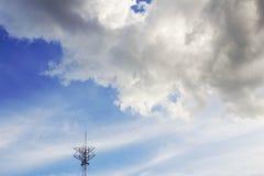 Moln och antenner på himmel Arkivbild