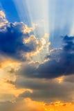 Moln och en blå himmel med en solstråle som igenom skiner Arkivbild