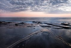 Moln- och havskust efter solnedgång på den La Jolla lilla viken i sommaren royaltyfri fotografi