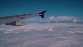 Moln och Himalayas under vingen av ett flygplan lager videofilmer