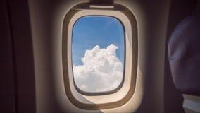 Moln och himmel som sett igenom fönster av ett flygplan arkivbilder