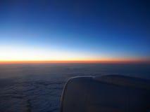 Moln och himmel till och med fönster av flygplanet på nattetid Arkivbild