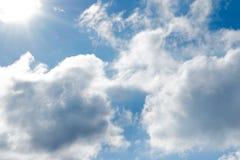 Moln och sol i blå himmel Arkivbild