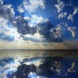Moln och solljus som reflekterar i sjön Arkivbild
