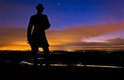 Moln och stjärnor som flyttar sig bak en staty i en lång exponering som tas på natten från liten rund överkant i Gettysburg, Penns Arkivbilder