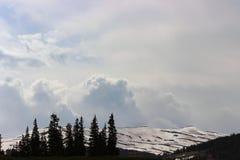 Moln ovanför de steniga bergen royaltyfria bilder