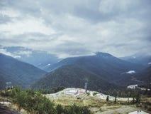 Moln ovanför den dimmiga byn för bergskogvändkrets Royaltyfria Foton