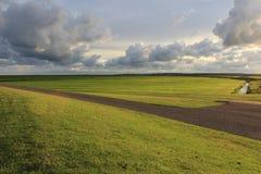 moln ovanför polder på Terschelling Arkivbild