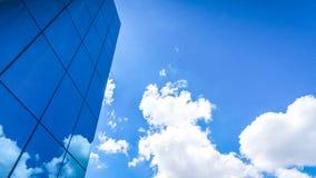 moln reflekterade i de många spegelförsedda fasetterna av ett modernt kontor Arkivfoto
