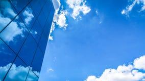 moln reflekterade i de många spegelförsedda fasetterna av ett modernt kontor Royaltyfri Foto