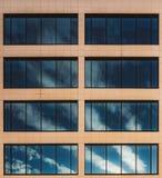 Moln reflekterade i fönster av en kontorsbyggnad arkivfoto