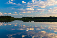 Moln reflekterade i floden arkivfoto