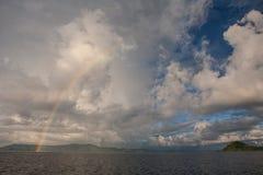 Moln, regnbåge och öar Fotografering för Bildbyråer