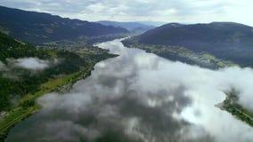 Moln rullar över den alpina sjön i berg stock video