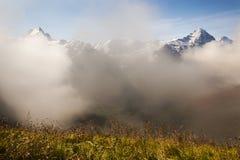 Moln Schreckhorn och framsidan av Eigeren i de schweiziska fjällängarna Arkivbild