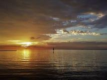Moln som bryter på soluppgång över vatten Royaltyfria Bilder