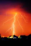 Moln som grundar elektrisk blixt bak hustakblast royaltyfria foton