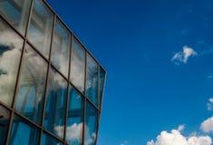 Moln som reflekterar i glass byggnad royaltyfria foton