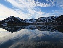 Moln som reflekterar i lugna vatten, Svalbard, Norge Royaltyfri Fotografi