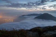 Moln som rullar över ett berg på den Lantau ön på gryning Royaltyfria Foton